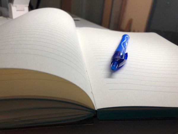A photograph of an open notebook and pen.